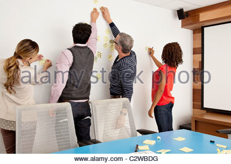 Business people putting adhesive notes on conference room wall - Stockfoto