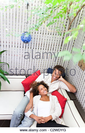 Couple laying together on sofa - Stock Photo