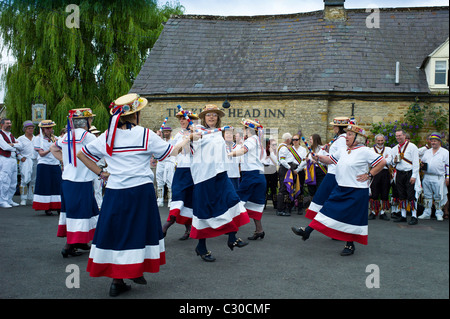 England's Glory Ladies Morris dancers perform a dancing display at The Kings Head Pub in Bledington, Oxfordshire, - Stock Photo