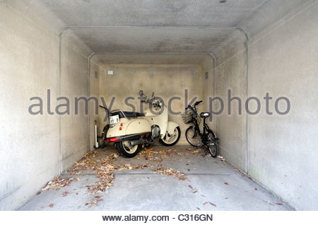 one car parking garage with a bicycle and a motorcycle - Stock Photo