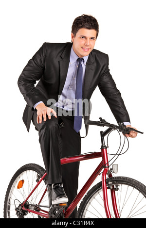 A young businessman posing on a bicycle - Stock Photo