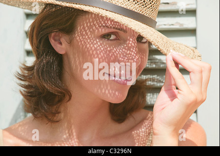 Woman wearing a sun hat with shadows on face - Stock Photo