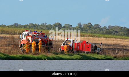 Volunteer Firefighters at their fire trucks after attending a grass fire. Pokolbin, Hunter Valley, NSW, Australia. - Stock Photo