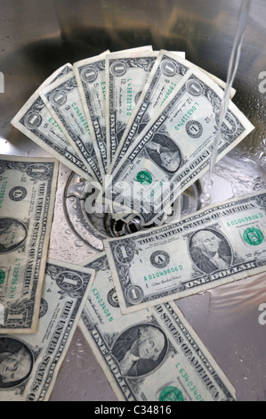 US dollars in a sink drain with water running concept good money going down the drain. - Stockfoto