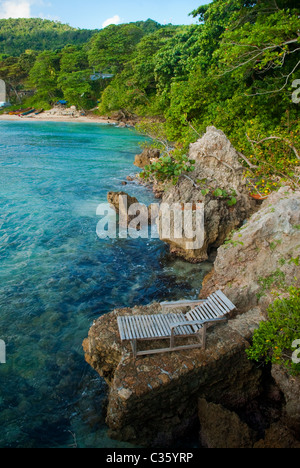 Wooden lounge chair at the beach cove at Great Huts eco-resort, Boston Bay, Portland, Jamaica - Stock Photo