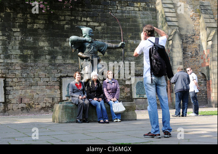 Stock photo of tourists having their photo taken at the Robin Hood statue in Nottingham. - Stock Photo