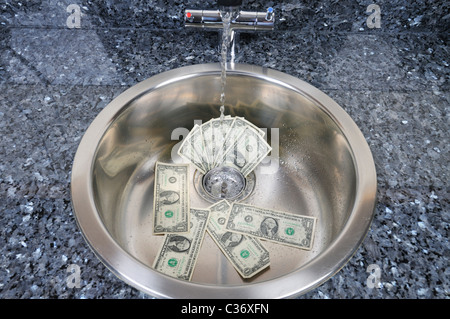 Sink with US dollar bills in drain with water running concept 'money going down the drain' - Stockfoto