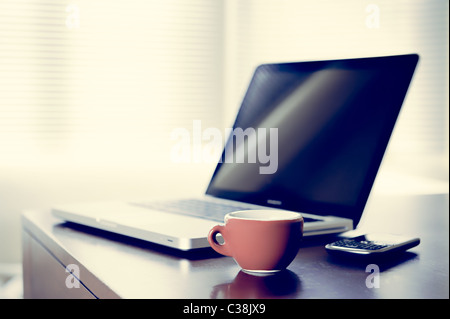 coffee break concept, the image show a laptop, mobile phone and a cup of coffee on the desk in background a big - Stock Photo