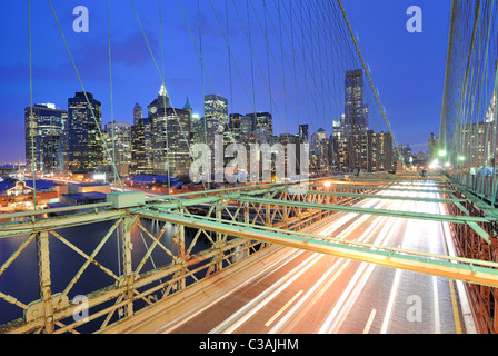 View of downtown Manhattan from the Brooklyn Bridge with traffic flying by. - Stockfoto
