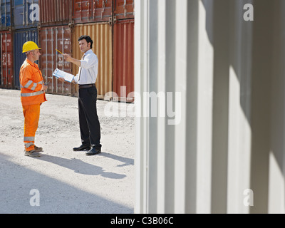 mid adult businessman and manual worker standing near cargo containers. Horizontal shape, full length, copy space - Stock Photo