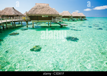 Over water bungalow with steps into amazing green lagoon - Stock Photo