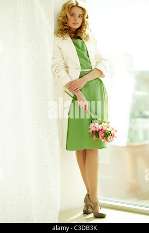 Beautiful woman in elegant clothes standing by the window - Stock Photo