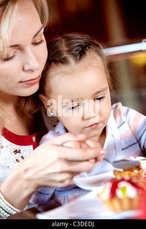 Portrait of cute girl eating cupcake with her mother near by in cafe - Stock Photo