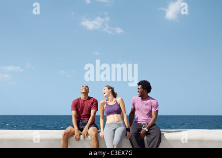 caucasian, hispanic and african american friends smiling and having fun near the sea. - Stock Photo