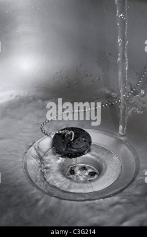 Water Running Down the Plug Hole in Kitchen Sink - Stock Photo
