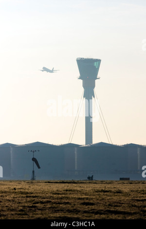 Comercial airliner taking off and London's Heathrow control tower. - Stock Photo