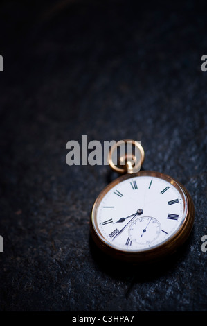 Old open face pocket watch on slate - Stock Photo