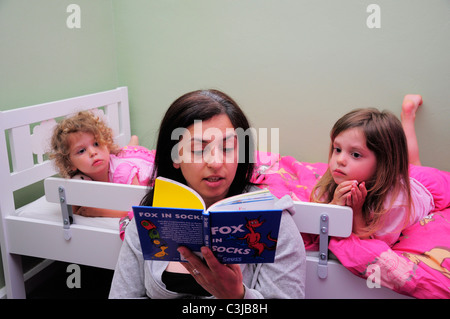 Mother reading a Dr Suess childrens story to her daughters at bedtime. - Stock Photo