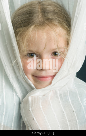 Germany, Bavaria, Girl playing hide and seek, close up - Stock Photo