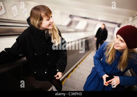 Two teenage girls (14-15) on escalator - Stock Photo