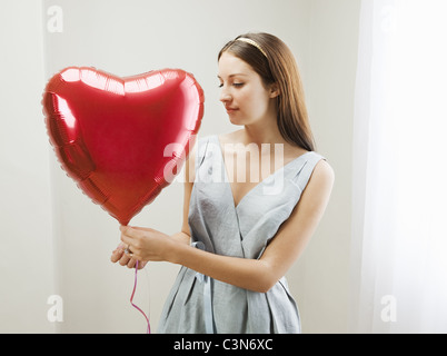 Woman holding heart shaped balloon - Stockfoto