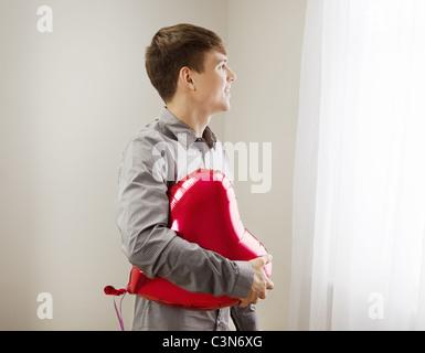 Man holding heart shaped balloon - Stockfoto
