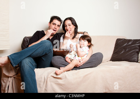 Beautiful happy family, father mother toddler daughter child, eating snacks while sitting on sofa couch in livingroom. - Stock Photo