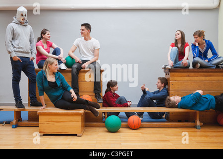 Germany, Berlin, Young and teenage people sitting in school gym - Stock Photo