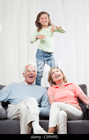 Granddaughter (6-7) dancing and grandparents enjoying, smiling - Stock Photo