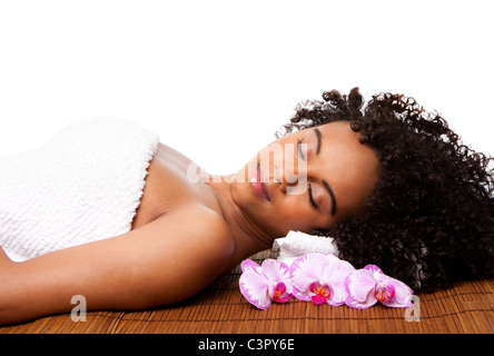 Brazilian woman at a day spa, laying on bamboo massage table with head on pillow wearing a towel and orchid flowers - Stock Photo