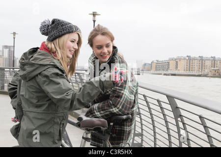 2 young women with push bikes - Stock Photo