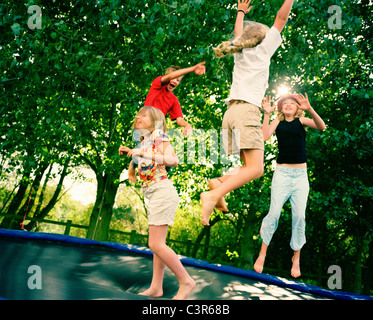 4 children leaping on trampoline - Stock Photo