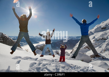Happy family jumps in winter mountains - Stockfoto