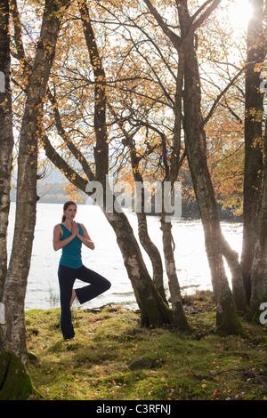 woman practising yoga position amongst trees - Stock Photo