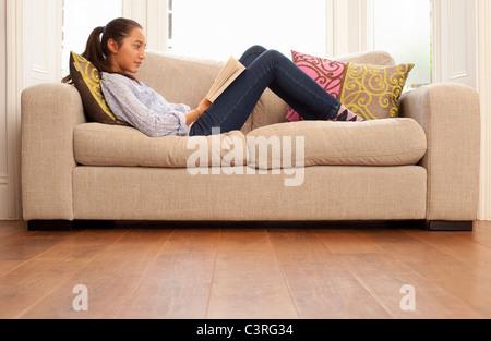 teenage girl reading on sofa - Stock Photo