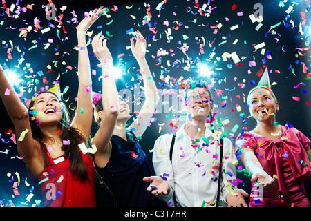 Four friends making having fun among confetti - Stock Photo