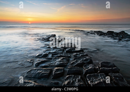 Sunset over the Bristol Channel as seen from the dramatic rocky shores of Nash Point in Southern Wales - Stock Photo