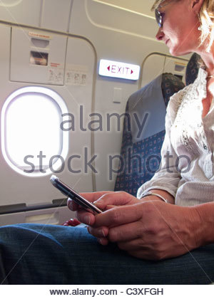 Close up of woman text messaging on cell phone in airplane - Stock Photo
