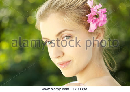 Portrait of young woman with pink flower in hair outdoors - Stock Photo