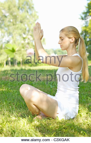 Portrait of young woman practicing yoga in grass - Stock Photo