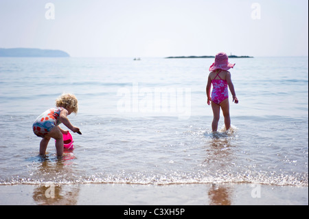 Horizontal portrait of two little girls paddling in the sea on the beach on a sunny day. - Stock Photo
