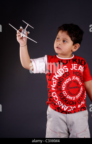 Little boy is playing with toy airplane - Stock Photo
