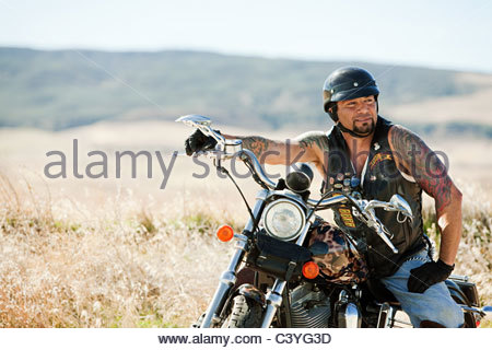 Portrait of man parked on motorcycle - Stock Photo