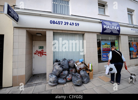 A passer by outside a branch of the Halifax Bank in Cheltenham UK - Stock Photo
