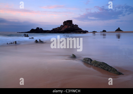 Sunset on the beautiful beach at Praia de Castelejo near Villa do Bispo in the Algarve region of Portugal - Stock Photo