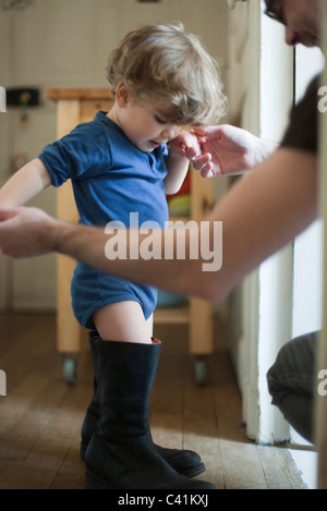 Toddler boy learning to walk in father's boots - Stock Photo