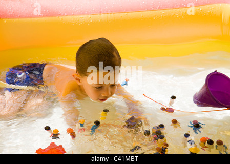 Little boy playing with toys in wading pool - Stock Photo