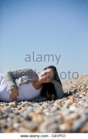 A pregnant woman lying on the beach, smiling - Stockfoto