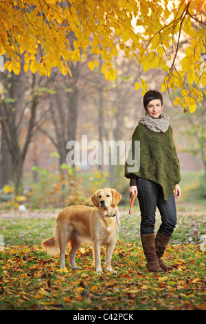 Young girl and her dog (Labrador retriever) walking in autumn in a city park - Stock Photo