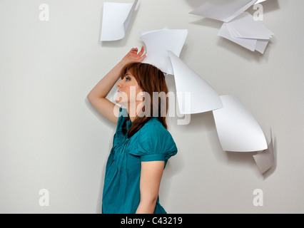 Young woman throwing paperwork in air - Stockfoto